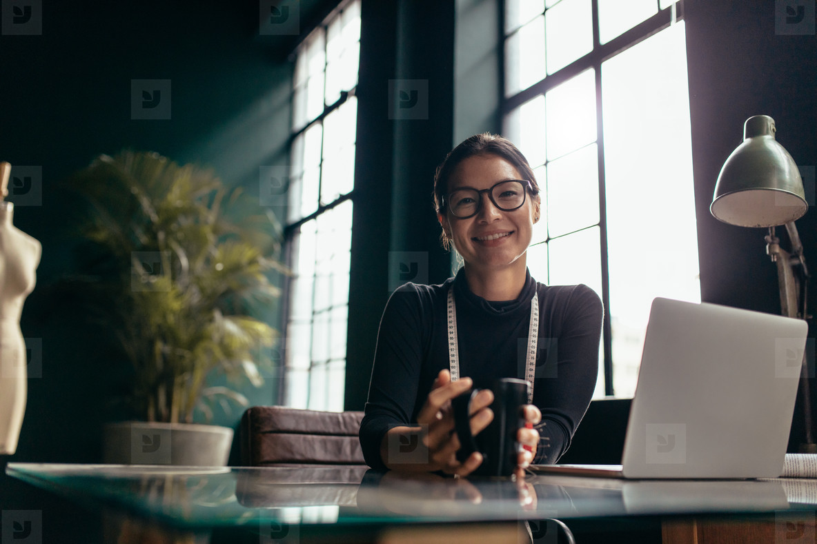 Creative female sitting in office with coffee