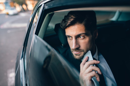 Young business man travelling by a car