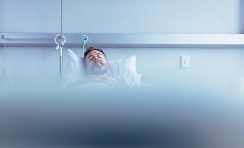 Mature sick male patient sleeping in hospital bed