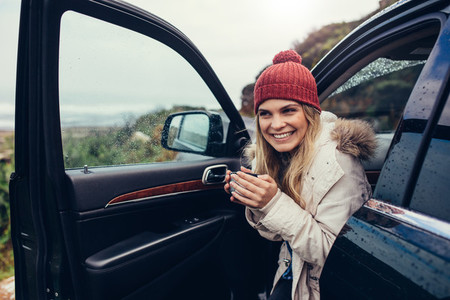 Beautiful smiling woman in her car drinking coffee