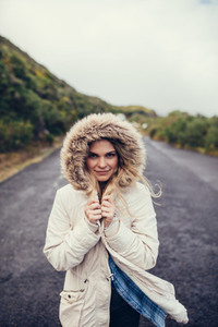 Woman in warm clothing on open road