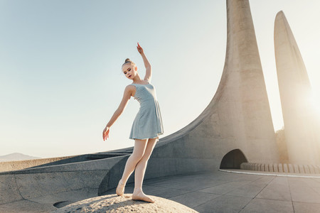 Female ballet dancer practicing dance moves on a rock