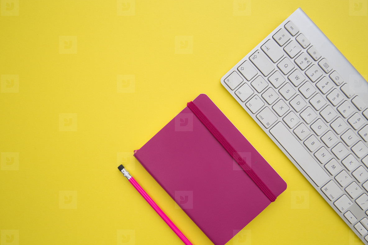Computer keyboard and notebook on bright yellow background works