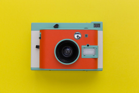 Cute retro camera overhead on bright yellow background