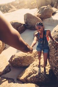 Man helping woman climbing rock at the beach