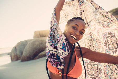 African woman holding scarf on the beach