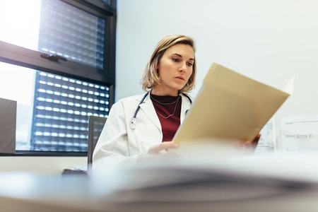 Female doctor studying medical records