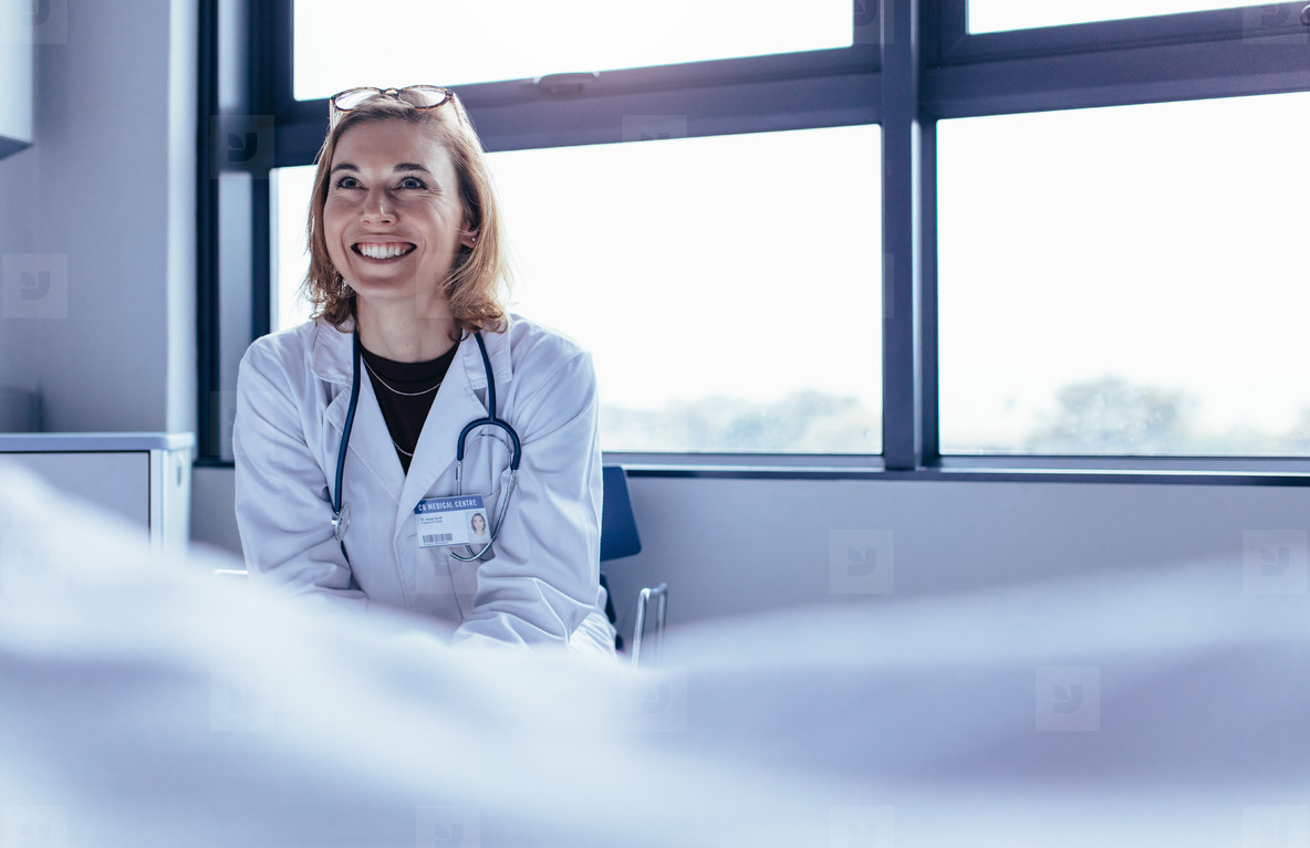 Happy female doctor sitting in hospital room