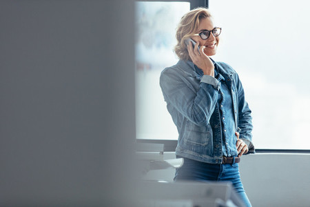 Smiling woman talking on smartphone in workplace