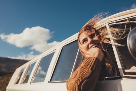 Traveling female driving the van and enjoying road trip