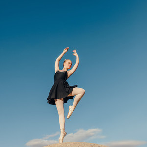 Female ballet dancer practicing dance moves on a rock top