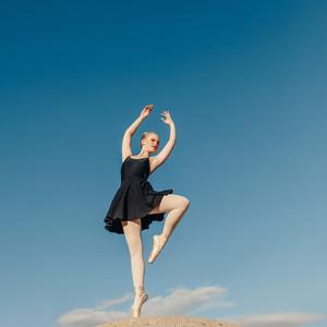 Female ballet dancer practicing dance moves on a rock top