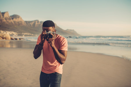 Man taking photos with digital camera at beach