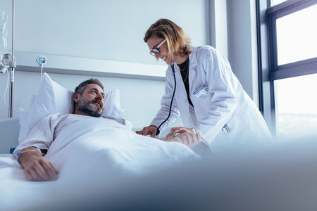 Doctor examining patient pulse in hospital room