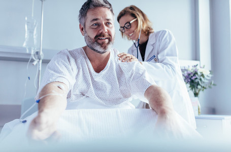 Mature man sitting in hospital bed and physician doing checkup