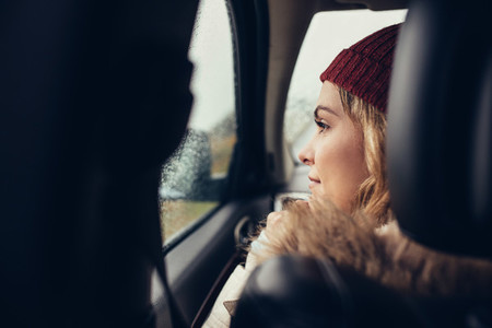 Woman traveling by car and looking outside window