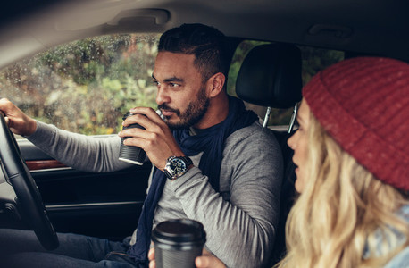 Couple drinking coffee while driving a car