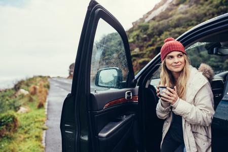 Woman having coffee during road trip