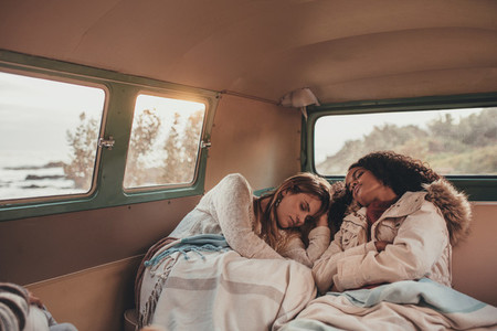 Women friends sleeping in the van