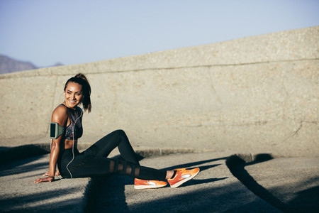 Healthy woman sitting on steps after exercising