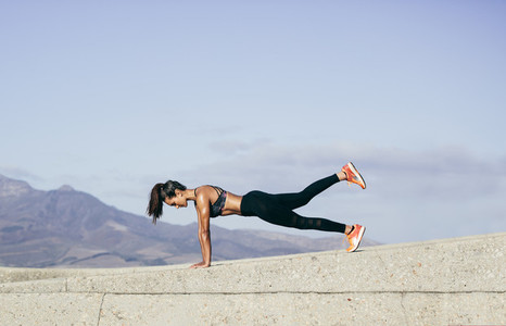 Muscular woman doing core exercise outdoors