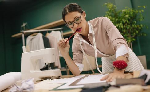 Female tailor thinking over new dress design