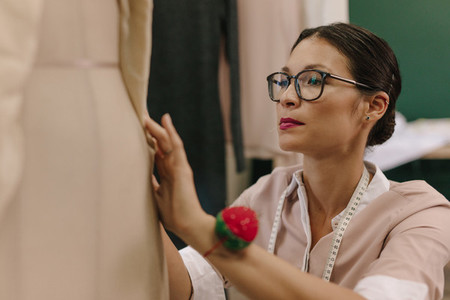 Fashion designer fixing dress on mannequin