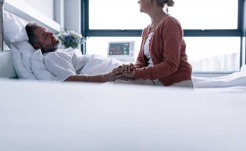 Woman visiting husband in hospital ward