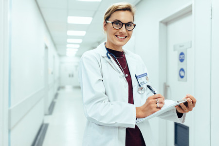 Smiling doctor standing in hospital corridor with clipboard