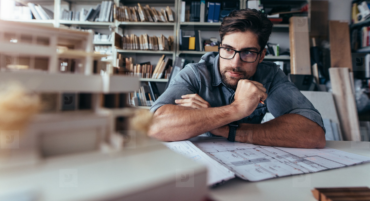 Architect looking at house model on desk