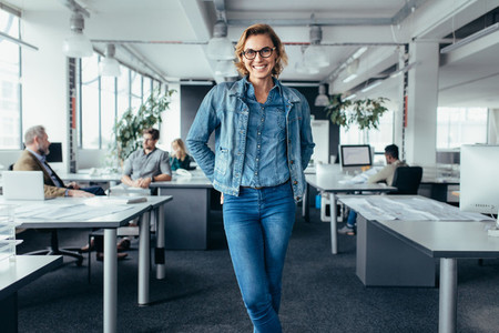 Cheerful businesswoman standing in office environment