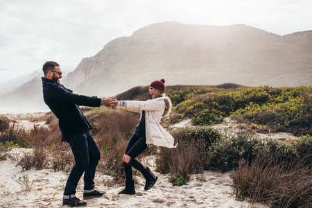 Beautiful couple dancing along the beach on winter day