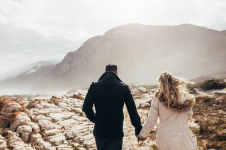 Couple walking through rocky coastline on a winter day