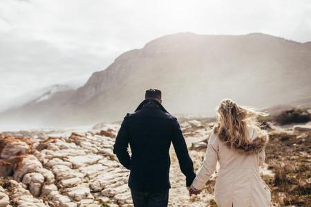 Couple walking through rocky coastline on a winter day