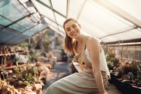 Beautiful gardener smiling at plant nursery