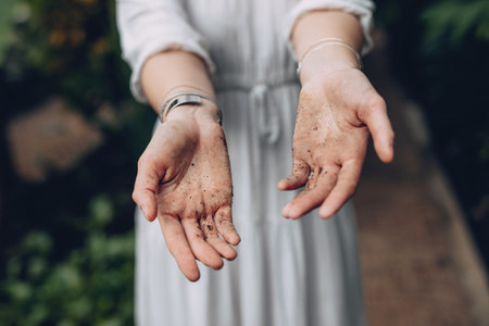 Woman with hands covered in dirt