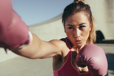 Female boxer practicing boxing outdoors