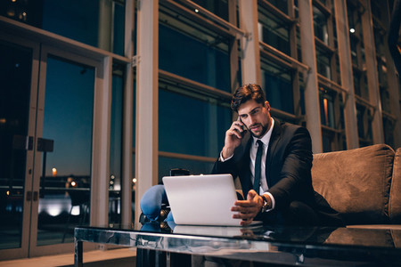 Businessman at airport lounge using laptop and cellphone