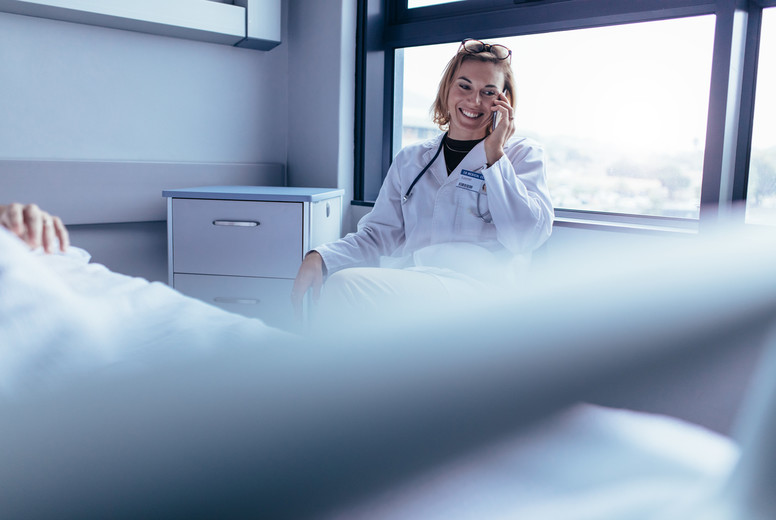 Happy female doctor sitting in hospital room and making a phone