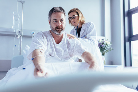 Doctor examining mature man in hospital bed