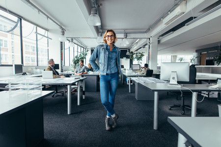 Young businesswoman standing in office with colleagues