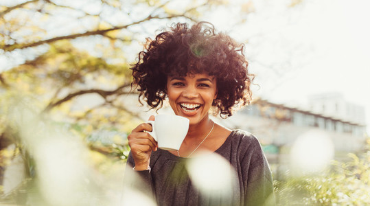Portrait of a happy young woman drinking coffee