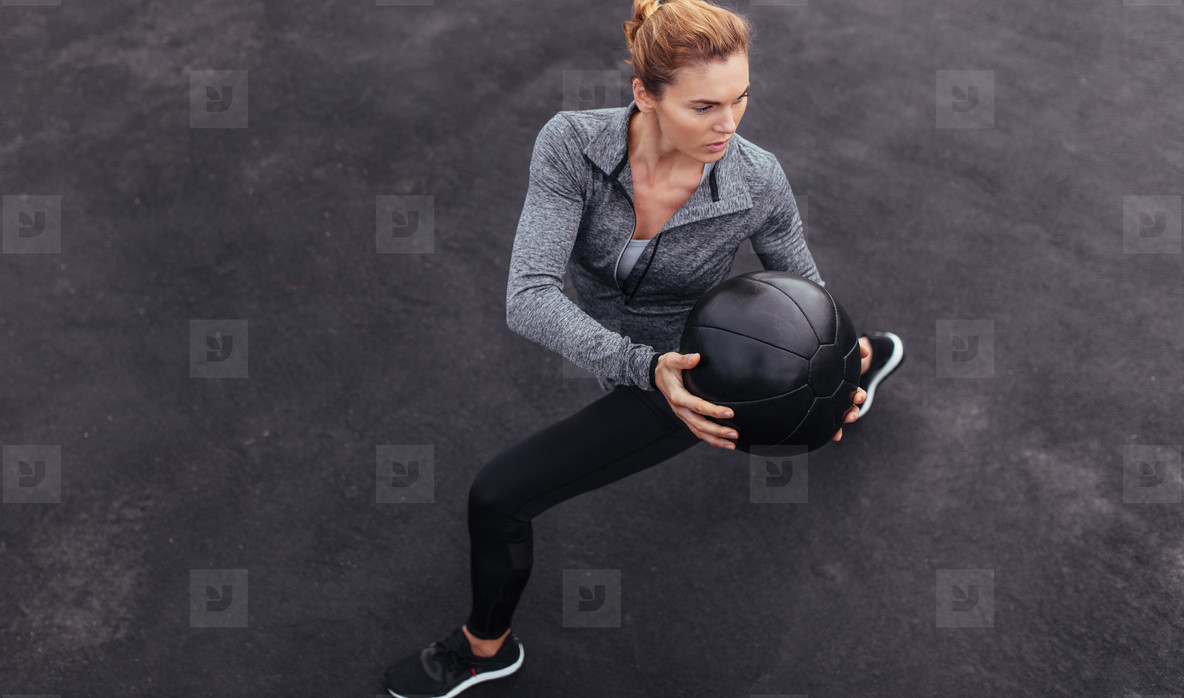 Fit woman exercising outdoors with medicine ball