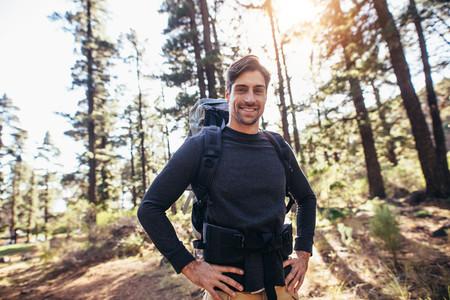 Man walking in forest wearing a backpack