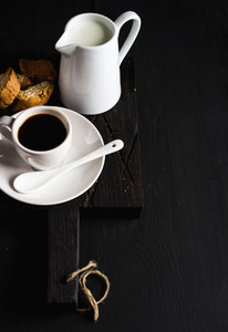 Cup of hot espresso  creamer with milk and cookies on dark rustic wooden board over black background  copy space