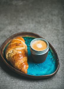 Cup of espresso and croissant in blue tray  grey background