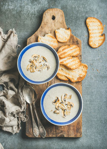 Creamy mushroom soup in bowls with toasted bread slices