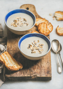 Creamy mushroom soup in bowls with grilled bread slices