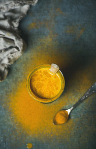 Golden milk with turmeric powder in glass over dark background