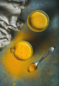 Golden milk with turmeric powder in glasses over dark background